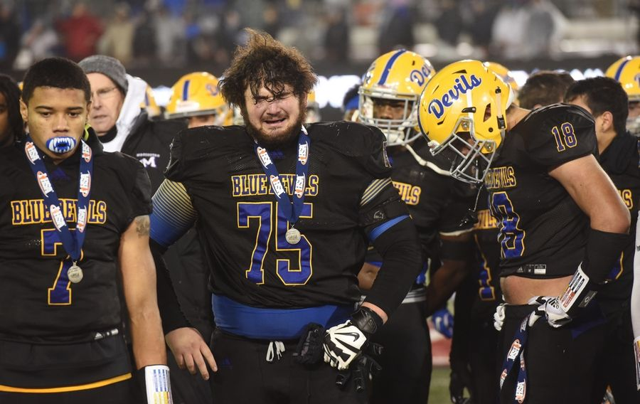 Warren players, from left, Josh Turner, Matt Rich and Juan DelaCruz react to their team's 12-0 loss to Lincoln-Way East during the IHSA Class 8A state football championship game at Northern Illinois University in DeKalb Saturday.